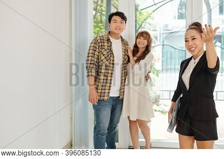Happy Vietnamese Real Estate Manager Showing Big Hall Of New House To Young Couple