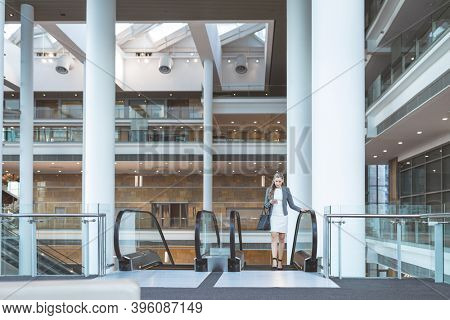 Front view of businesswoman using mobile phone on escalator in a modern office building
