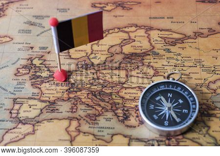 Flag Of Belgium And Compass On The World Map.