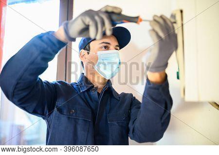 Smiling technician repairing an hot-water heater wearing a mask due to coronavirus pandemic