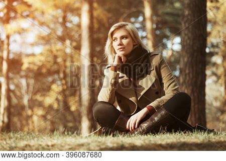 Happy young blonde fashion woman sitting on grass in autumn park Stylish female model in classic beige coat and black scarf
