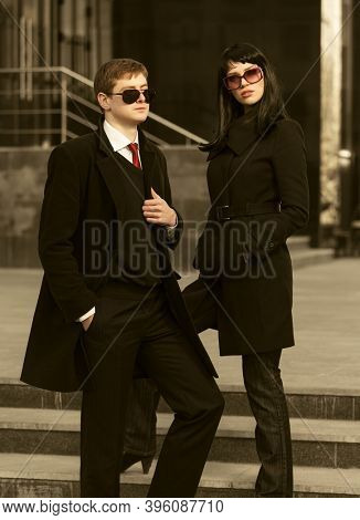 Young fashion business couple on city street Stylish man and woman in classic black coats and sunglasses