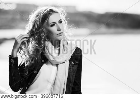 Young blonde woman with long curly hairs  Stylish fashion model in denim jacket and white scarf