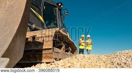 Workers discussing their job in quarry or gravel pit standing on sand hill with bulldozer