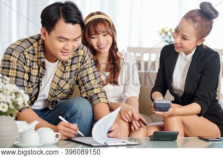 Happy Young Vietnamese Couple Signing Contract With Real Estate Manager And Paying For Her Service
