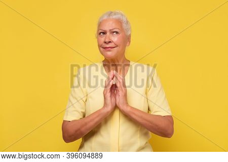 Senior Confident And Tricky Woman Holding Fingers Together And Smirking Aside, Having Some Tricky Id