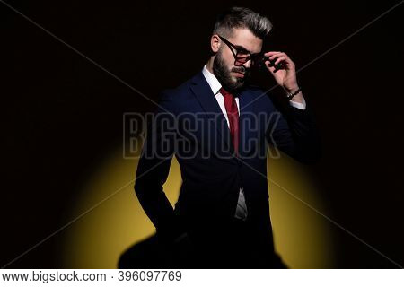 cool elegant businessman in navy blue suit holding hand in pocket, looking down and adjusting glasses, standing in a fashion light on a yellow background in studio