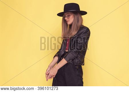 attractive casual woman with cool style is looking down and holding her hands together