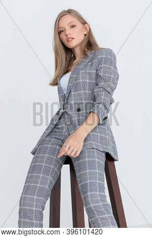 cool blonde model in gray checkered suit looking down and confidently posing, sitting on light gray background in studio