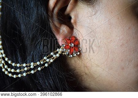 Side View Of Girl Face Wearing Golden Earring With Red Stone