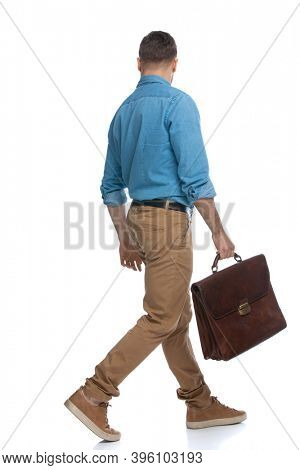 rear view of a casual guy walking one way and looking the other way while holding his briefcase against white background