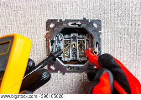 Measuring The Readings Of An Electrical Outlet With A Multimeter. Hands In Red Work Gloves Hold Test