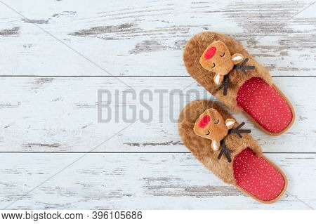 Cozy Christmas Slippers On Wooden Parquet Top View. Christmas Celebration At Home.