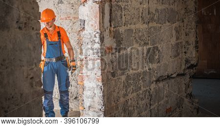 Caucasian Builder Contractor In His 40s And Old Building Remodeling And Restoration Job. Industrial