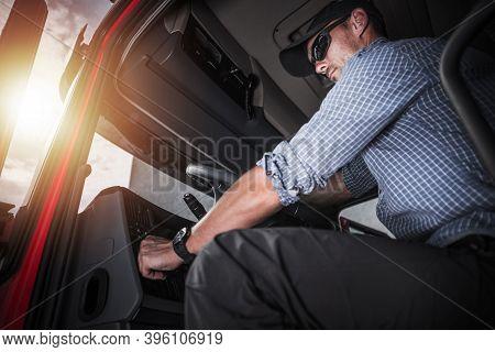 Caucasian Semi Truck Driver Wearing Black Baseball Hat Inside Vehicle Cabin Preparing To Hit The Roa