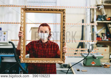 Woman worker with face mask after doing a wooden frame renovation and refurbishment. Industry and work during coronavirus Covid-19