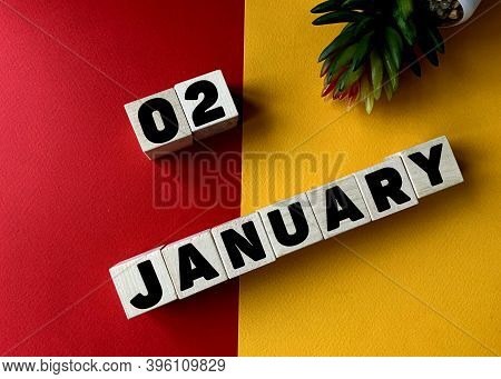 January 2 In Black Letters On Wooden Blocks On A Divided Yellow-red Background .next To A Flower .ca