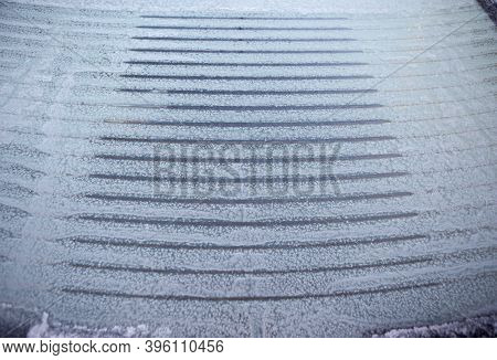 Heated, Ice-covered Rear Window Of A Car When Defrosting On A Frosty Winter Morning