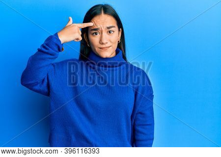 Young asian woman wearing casual winter sweater pointing unhappy to pimple on forehead, ugly infection of blackhead. acne and skin problem