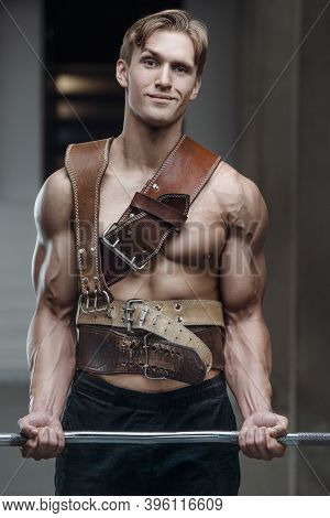 Caucasian Power Athletic Man Training Biceps Muscles With Athletic Belt. Strong Bodybuilder With Six