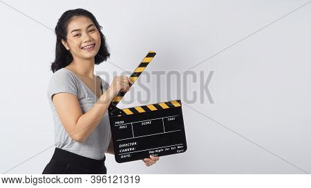 Teenage Girl Or Woman Wearing Braces And Contact Lenses. Her Hand's Holding Black Clapper Board Or M