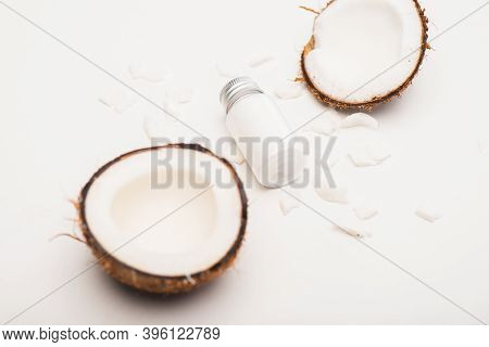 Bottle Of Homemade Lotion Near Coconut Halves And Flakes On White Surface