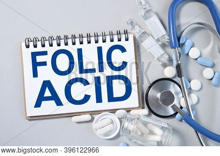 Folic Acid. Text On White Paper On A Gray Background. Stethoscope. Medicine Concept