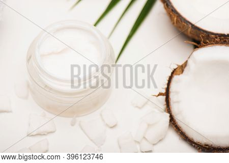 Container With Homemade Cream Near Palm Leaves, Coconut Halves And Flakes On White