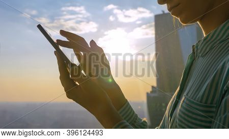 Woman Using Smartphone Device Against Sunset Cityscape View Through Window Of Skyscraper: Scrolling