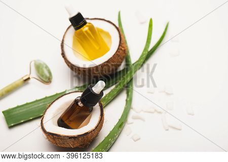 Bottles With Essential Oil, Jade Roller, Coconut Halves And Flakes Near Aloe Vera Leaves On White Bl