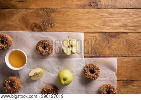 Baked Apple Cider Donuts With Apple Fruits And Cider On Baking Sheets On Natural Wooden Table. Ready