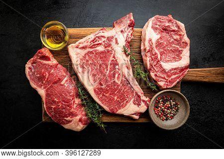Variety Of Fresh Raw Black Angus Prime Meat Steaks T-bone, New York, Ribeye And Seasoning On Black B