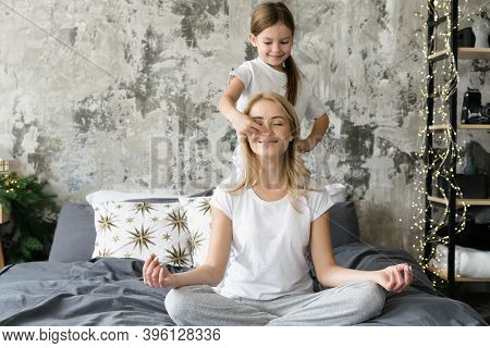 Smiling Mother Sitting On Bed In Meditating Pose While She Little Daughter Touching Her Nose. Mom An