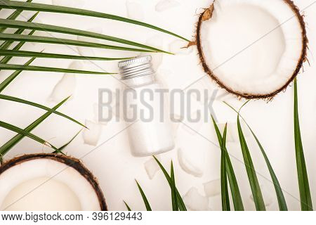 Top View Of Coconut Halves, Flakes, Bottle Of Homemade Lotion And Palm Leaves On White