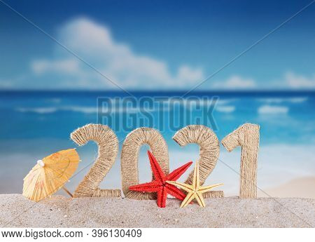 New Year On The Beach. Inscription 2021 From Twine And Starfishes In The Sand Against The Background