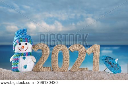 Happy Snowman And The Inscription 2021 In The Sand On The Beach Against The Background Of The Sea