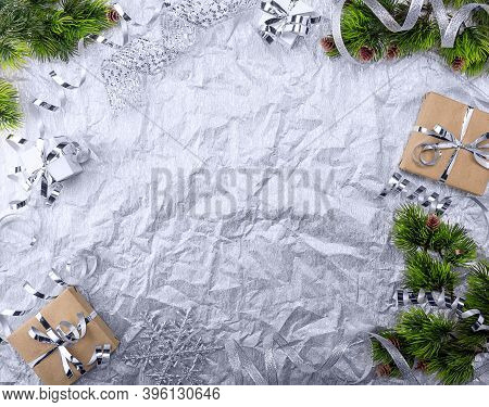 Christmas Card. Gifts With A Silver Ribbon And New Year Branches On A Light Textured Background