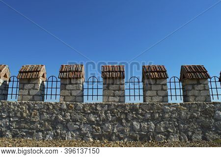 Rough Old Gray Stone Fence With Tiled Trellises And Posts. The Battlements Of The Fortress Wall Agai