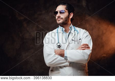 Self Confident And Brutal Doctor With Sunglasses In White Labcoat Poses With Crossed Arms In Dark Ba