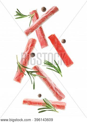 Cut Fresh Crab Sticks, Rosemary And Allspice Falling On White Background