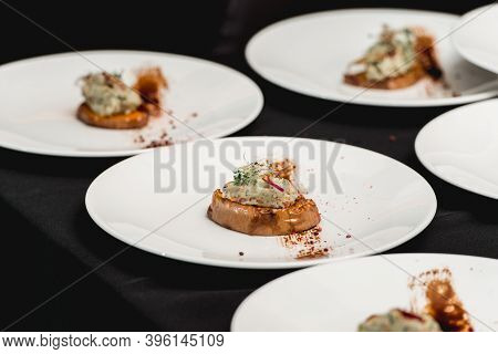 Several White Plates On A Black Table With Baked Sweet Pumpkin And Guacamole. Mexican Cuisine At The