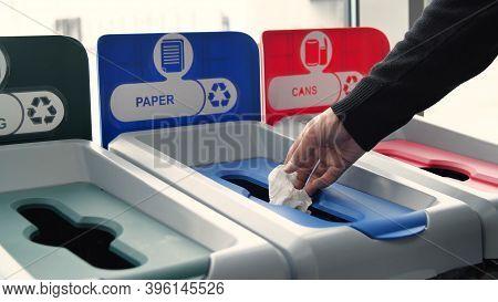 Close-up Of Man Throwing Garbage Into Sorting Bins. Media. Man Throws Garbage Into Colored Bins For