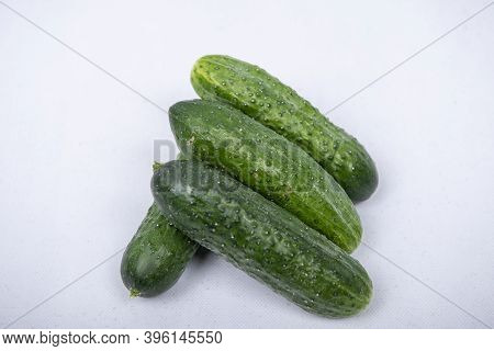 Fresh Cucumbers Are Standing On A White Background.
