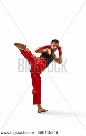 Athletic Man In Red Sports Bandages On His Hands Making Kick During Boxing Exercise, Isolated On Whi