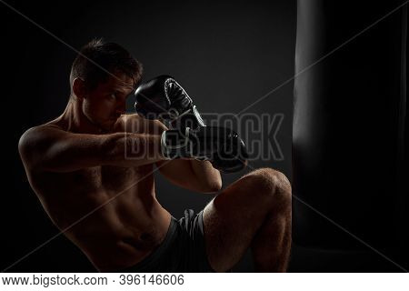 Muscular Boxer In Black Boxing Gloves Punching In Boxing Bag On Dark Background