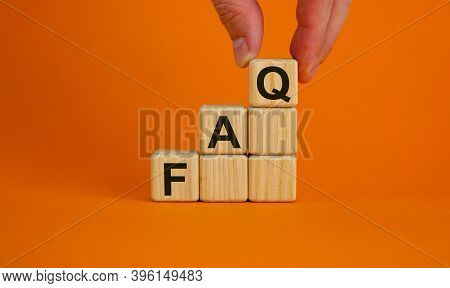 Concept Word 'faq, Frequently Asked Questions' On Cubes On A Beautiful Orange Background. Male Hand.
