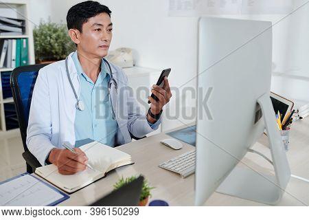 Mature Asian General Practitioner In Labcoat Working On Computer At His Desk And Taking Notes In Pla