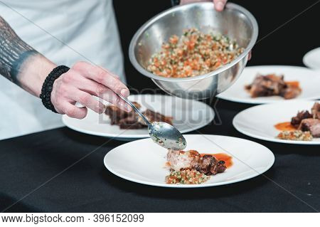 Chief Serving Homemade Bone-in Prime Rib Roast On A White Plate