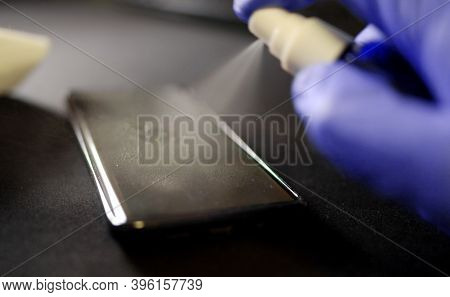 Hand In Protective Glove With Alcohol Spray Cleaning Mobile Phone. Covid-19 Disinfection Concept.