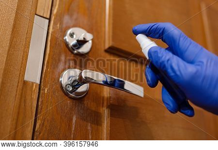 Hand In Protective Glove With Alcohol Spray Cleaning Door Handle. Covid-19 Disinfection Concept.